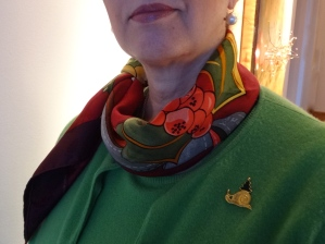 a scarf and a brooch add some charm